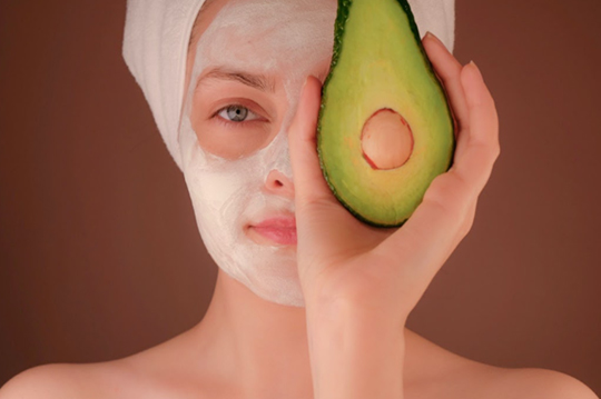 A woman wearing a cosmetic face mask while holding an avocado