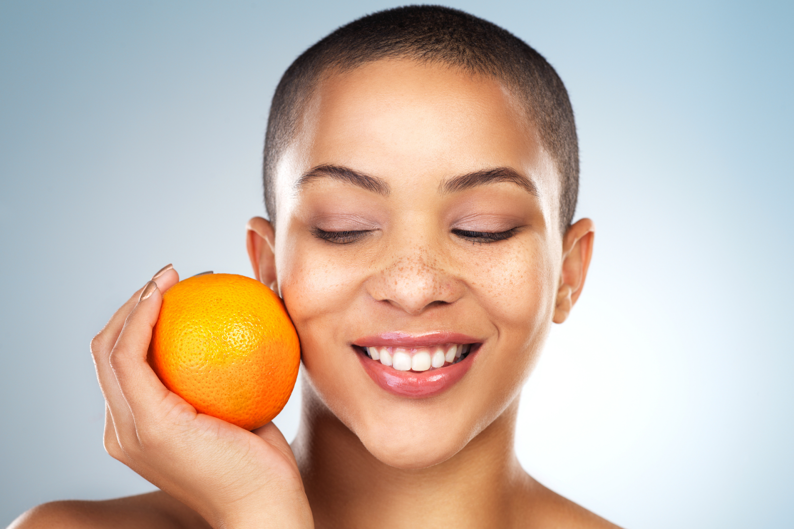 A woman with bright skin holding an orange
