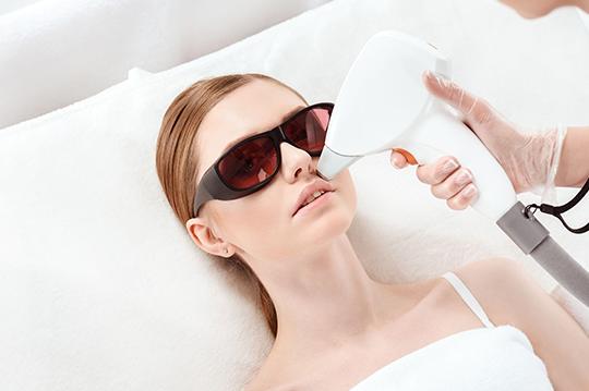A woman getting laser facial treatment